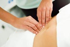 Manos que dan masajes al abdomen femenino El terapeuta que aplica la presión sobre sea Imágenes de archivo libres de regalías
