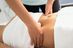 Manos que dan masajes al abdomen femenino El terapeuta que aplica la presión sobre sea Foto de archivo