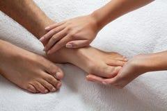 Manos que dan masajes a pies Foto de archivo libre de regalías