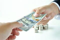 Manos que dan y que reciben el billete de dólar de Estados Unidos del dinero Fotografía de archivo libre de regalías