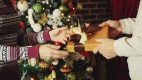 Manos que dan y que reciben la caja de regalo de la Navidad metrajes