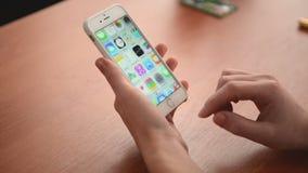 Manos que deslizan iconos del programa en un iPhone 6 almacen de video