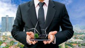 Manos que detienen al hombre de negocios en una turbina de viento limpia de la energía eléctrica del árbol del smartphone y una c fotos de archivo
