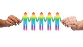Manos que detienen a la gente gay de cadena de papel Foto de archivo