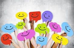 Manos que detienen a Smiley Faces Icons Imagen de archivo