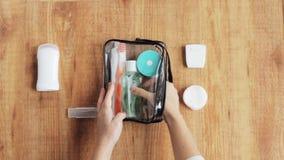 Manos que embalan el bolso cosmético para el viaje almacen de video