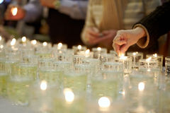 Manos que encienden velas fúnebres Fotos de archivo
