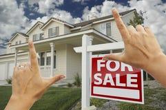 Manos que enmarcan la muestra de las propiedades inmobiliarias y la nueva casa Imágenes de archivo libres de regalías