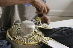 Manos que ensamblan un ventilador de techo Fotos de archivo libres de regalías