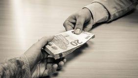 Manos que entregan el dinero Imagen de archivo