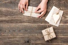 Manos que envuelven el sobre del arte y la caja de regalo de papel para el presente Fotografía de archivo libre de regalías