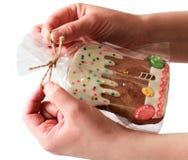 Manos que envuelven una galleta del jengibre Imagen de archivo libre de regalías