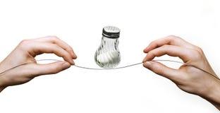 Manos que equilibran la coctelera de sal en el alambre Fotos de archivo