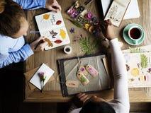 Manos que escriben el detalle de la colección secada de las flores en el cuaderno Han Foto de archivo