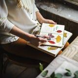 Manos que escriben el detalle de la colección secada de las flores en el cuaderno Han Imagen de archivo
