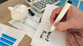 Manos que escriben mis metas financieras en un cuaderno de notas almacen de video