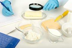 Manos que examinan la mantequilla en laboratorio del phytocontrol Imágenes de archivo libres de regalías