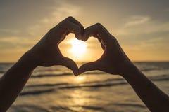 Manos que forman el corazón alrededor de puesta del sol Fotos de archivo