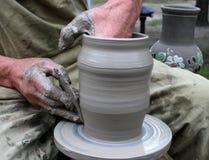 Manos que forman la arcilla en la rueda de alfarero Foto de archivo libre de regalías