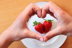 Manos que forman un corazón sobre dos fresas Imágenes de archivo libres de regalías