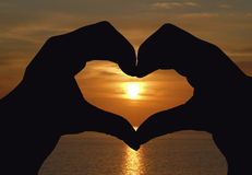 Manos que forman una dimensión de una variable del corazón Imagen de archivo libre de regalías