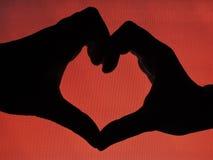 Manos que forman una dimensión de una variable del corazón Foto de archivo