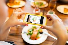Manos que fotografían la comida por smartphone Fotos de archivo libres de regalías