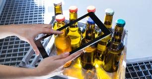Manos que fotografían las botellas de cerveza a través de la tableta digital en la cervecería Imagen de archivo