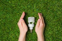 Manos que guardan cierre ahorro de energía de la lámpara del eco para arriba Imagen de archivo