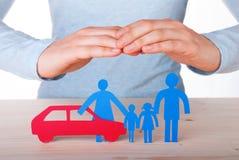 Manos que guardan la familia y el coche foto de archivo