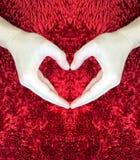 Manos que hacen el corazón en fondo mullido rojo Concepto del día del ` s de la tarjeta del día de San Valentín Concepto del amor Imagen de archivo libre de regalías