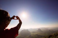 Manos que hacen forma del corazón contra el cielo de la salida del sol foto de archivo libre de regalías