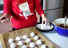 Manos que hacen las galletas del crujido y ponen pequeño pequeño b blanco Fotos de archivo libres de regalías