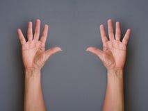 Manos que hacen las manos del aumento para arriba en fondo gris foto de archivo libre de regalías