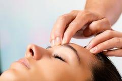 Manos que hacen masaje en la frente Fotografía de archivo