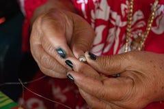 Manos que hacen necklage de la cáscara a mano de Polinesia foto de archivo