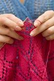 Manos que hacen punto una bufanda roja en fondo azul Foto de archivo