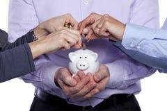 Manos que insertan el dinero en el piggybank Fotos de archivo