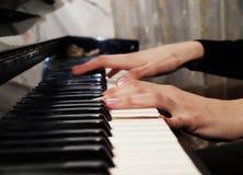 Manos que juegan el piano Fotos de archivo