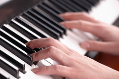 Manos que juegan música en el piano Foto de archivo libre de regalías
