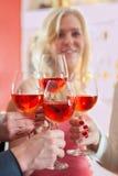 Manos que lanzan el vino rojo sobre los vidrios elegantes Foto de archivo libre de regalías