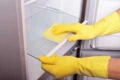 Manos que limpian el refrigerador. imagen de archivo libre de regalías