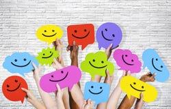 Manos que llevan a cabo burbujas del discurso con Smiley Faces Icons Imagenes de archivo