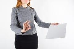 Manos que llevan a cabo documentos de firma de un papel en blanco del Libro Blanco aislados en el fondo blanco Imagen de archivo libre de regalías