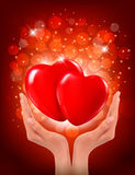 Manos que llevan a cabo dos corazones rojos. Vector ilustración del vector