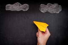 Manos que llevan a cabo el avión de papel amarillo debajo de las nubes fotografía de archivo