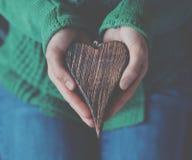 Manos que llevan a cabo el corazón de madera fotografía de archivo libre de regalías