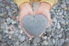 Manos que llevan a cabo el corazón - piedra en forma de corazón Imagen de archivo libre de regalías