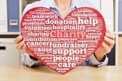 Manos que llevan a cabo el corazón con la nube de la etiqueta de la caridad Imagenes de archivo