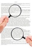 Manos que llevan a cabo el documento de la lectura de la lupa Imagenes de archivo